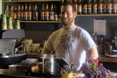 Employee Paul smiles behind the counter at Kaya Coffee House. Paul has bee working at Kaya for two years and has never gotten tired of the menu.