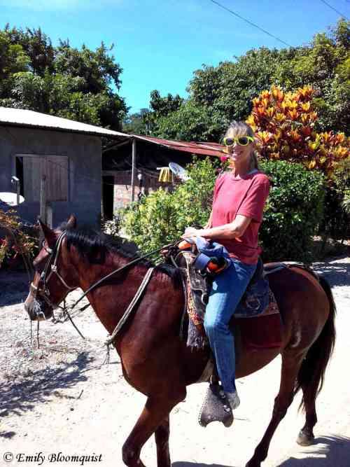 Carol riding through a small town