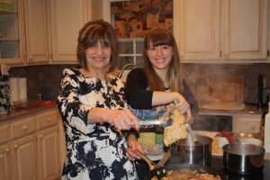 Annelise stirring the risotto as Sandi adds chicken to the reduced sauce