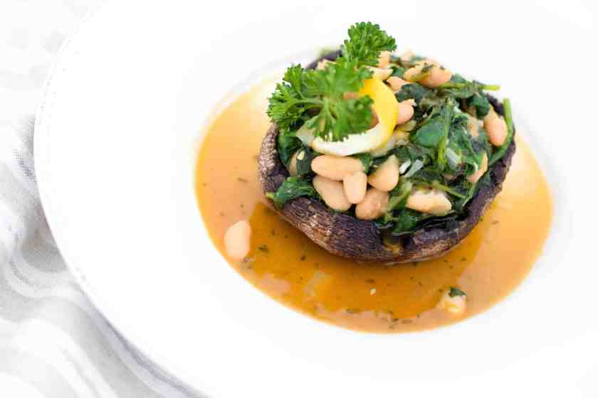 If you love garlic and lemon, this recipe is for you! Tender kale and white beans sauteed with lemon and garlic stuffed inside a baked portabella mushroom cap make this a perfect Meatless Meal! | @EmKyleNutrition