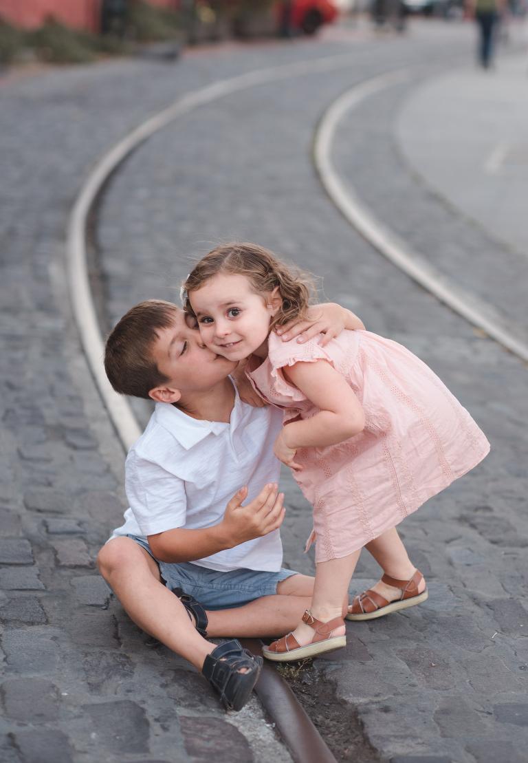 Petaluma sibling photography, downtown Petaluma, Petaluma trolley tracks, boy kissing girl on cheek, Saltwater sandals, Keen sandals, peach dress, white polo shirt, blue chino shorts