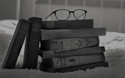 black and white photo of a stack of books with glasses on top