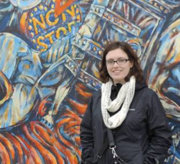 Emily standing in front of a mural
