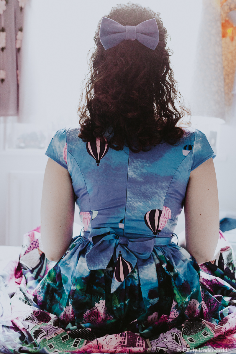 Blogger sitting on bed from behind looking out window, wearing a blue bow in her hair matching her dress.