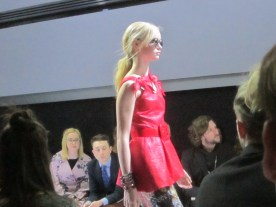 A blonde woman with a red dress with pink bows on the shoulders at Unbound, part of Julie Rovere's Neo Geo collection