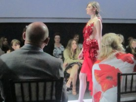 A brunette woman with blonde highlights walks in with a red dress with red flowers stitched on it, designed by Brandon R. Dwyer at Unbound 2016
