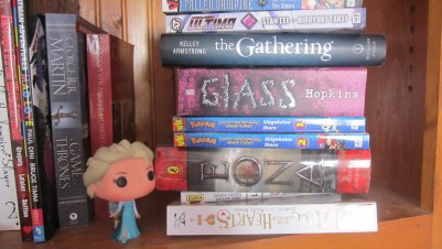 """An Elsa from """"Frozen"""" figurine nearby a bunch of books"""