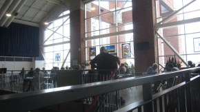 A man playing guitar, taken from the back, to people enjoying their lunch