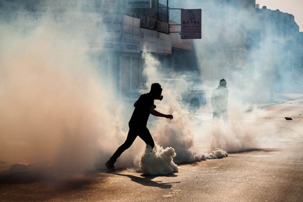 Bahraini protesters between the clouds of tear gas in clashes marking the fourth anniversary of the Gulf coalition,