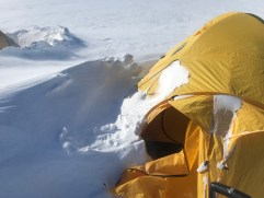 Tent partially buried by drifting snow