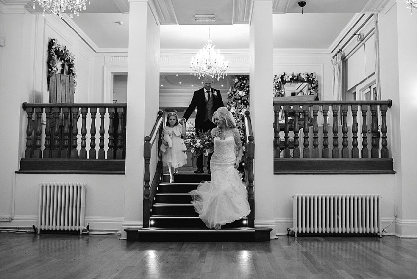 bride, groom and flower girl enter the room down the steps