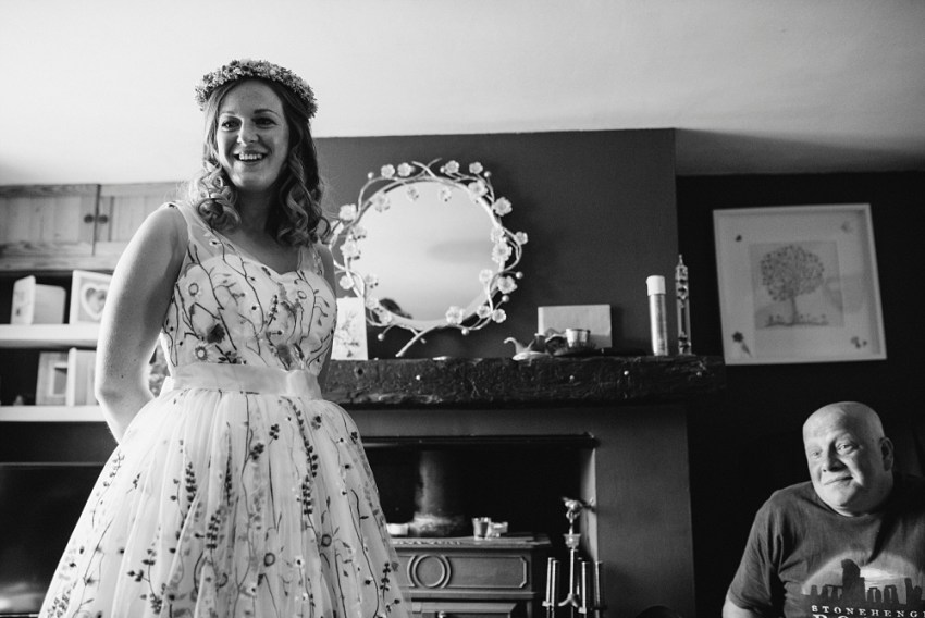 bride with flower crown and floral dress with her dad at home