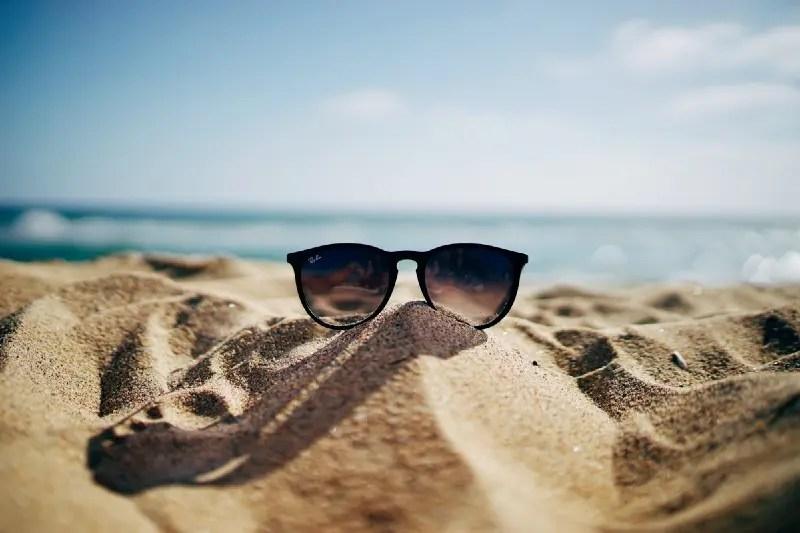 Happy summer scene of sunglasses on the beach.