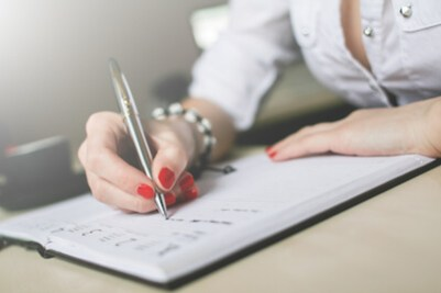 Ultimate checklist: how to overcome stress and anxiety. Woman writing in diary.