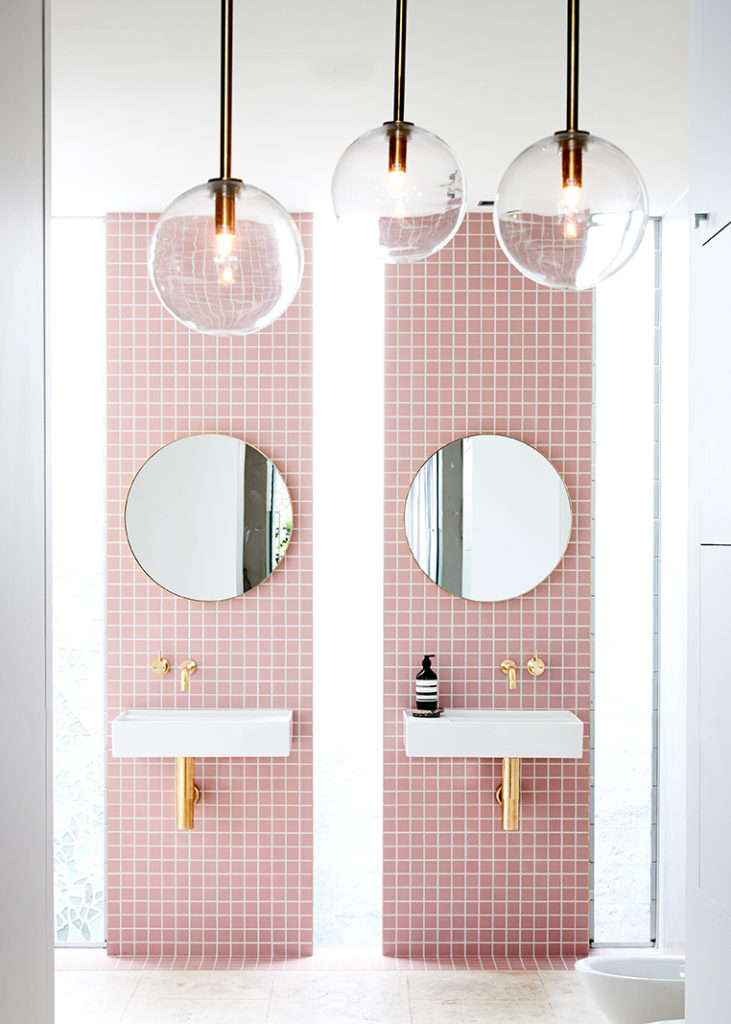 pink tiled bathroom with double vanity unit and brass hardware