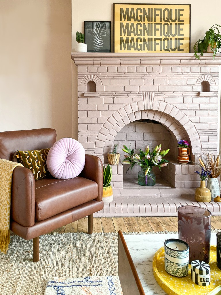 peach living room with pink fireplace and brown leather armchair