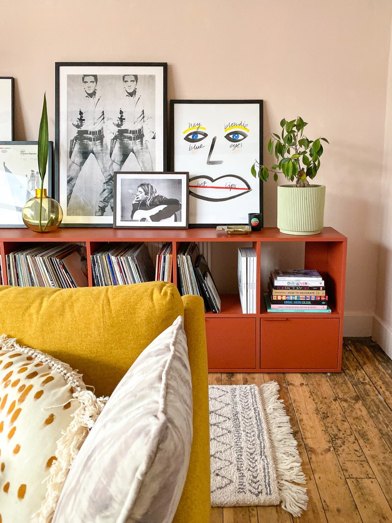peach living room with red shelving and framed artwork