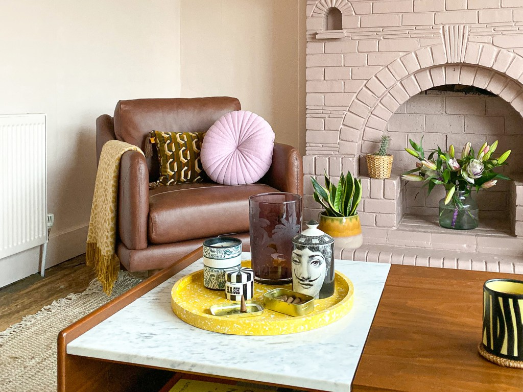 peach living room with pink fireplace and brown leather armchair and yellow accessories