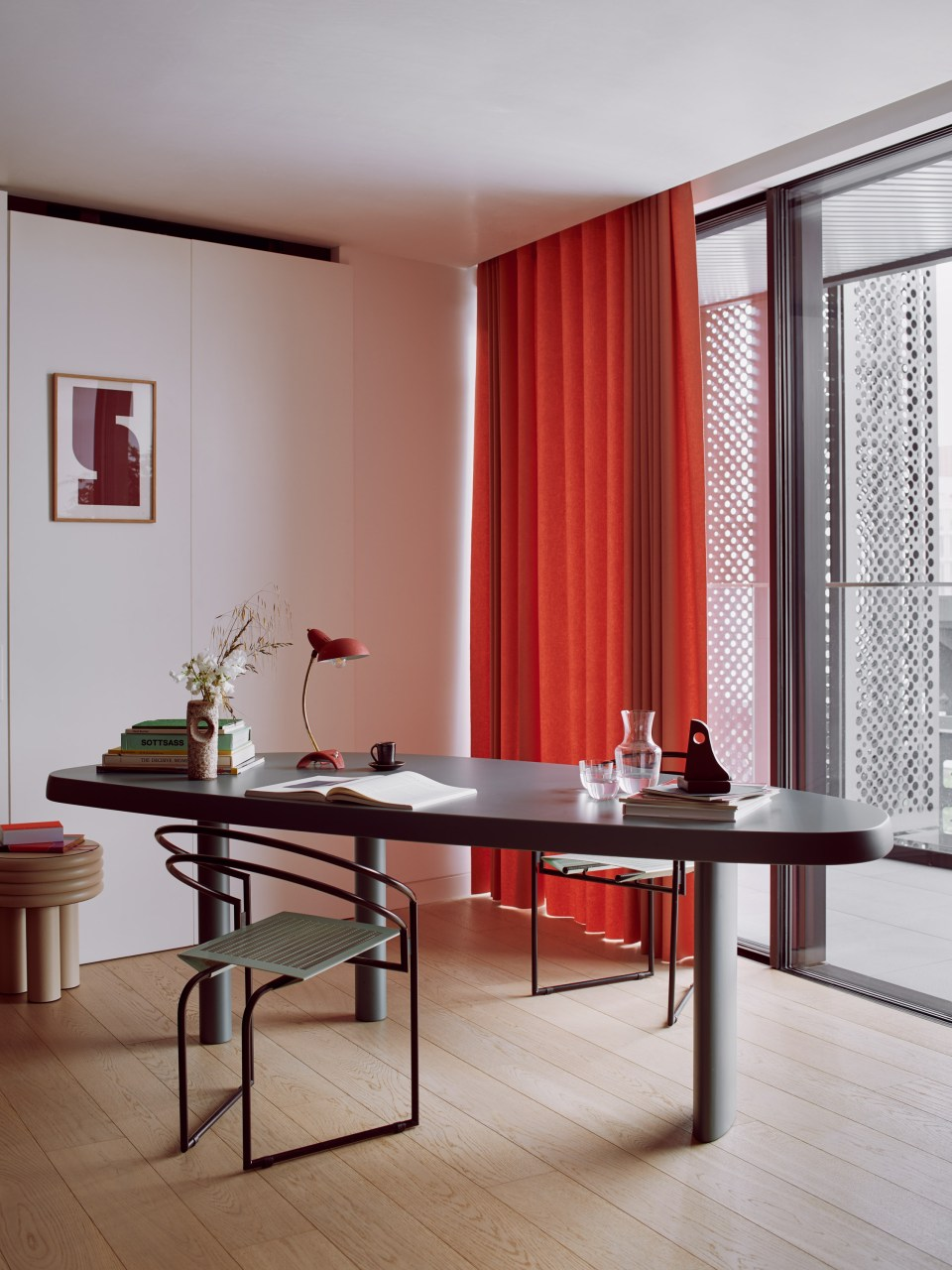 contemporary office with sculptural chairs and pink curtains