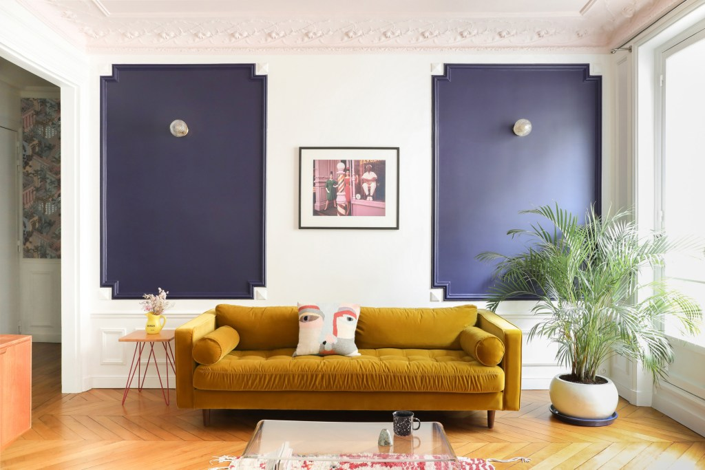 white living room with navy panelling and mustard sofa