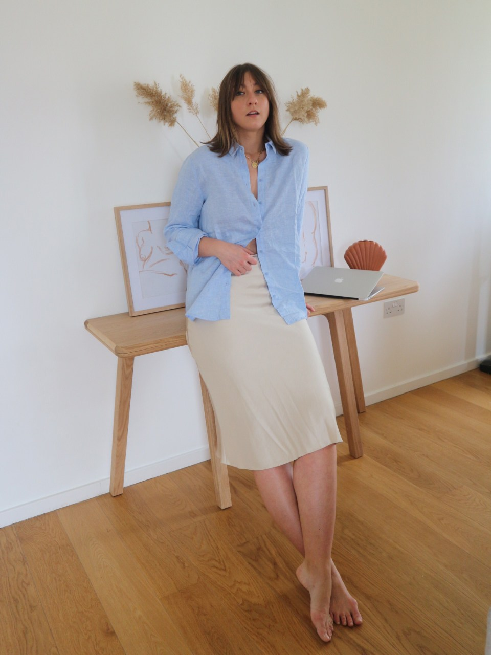 girl in shirt and skirt in front of wooden console in her flat