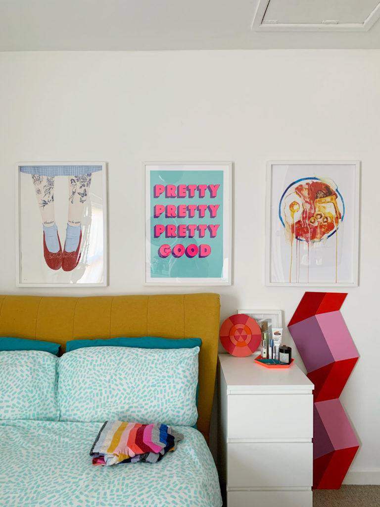 white bedroom with statement yellow bed and colourful prints