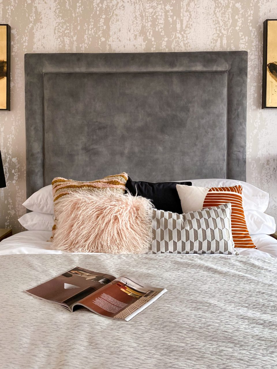 bed with giant grey headboard covered in pink, orange and navy cushions