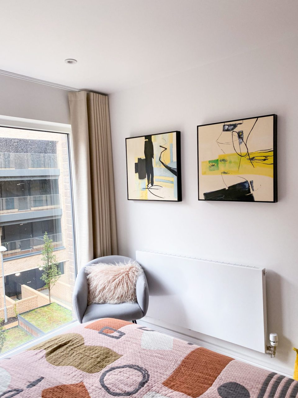 guest bedroom with yellow abstract artwork on the walls