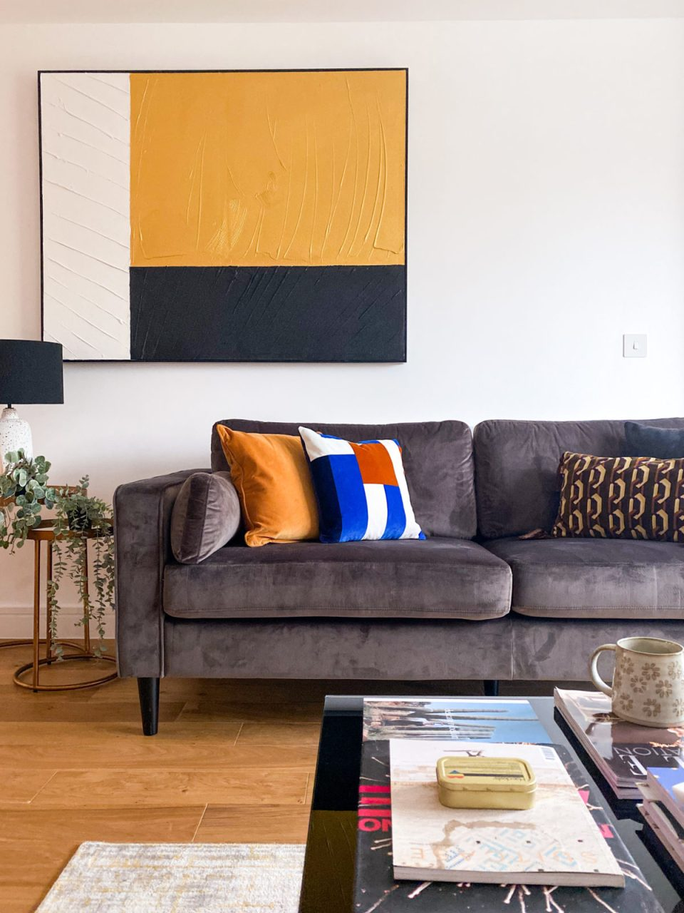 grey velvet sofa with mustard, orange and blue cushions and large abstract artwork in the background