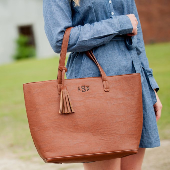 Leather tote bag with monogram and tassel detail by Carolina Dandy via 21 Festive Tassel Wedding Decorations & Accessories | http://emmalinebride.com/themes/tassel-wedding-decorations/ class=