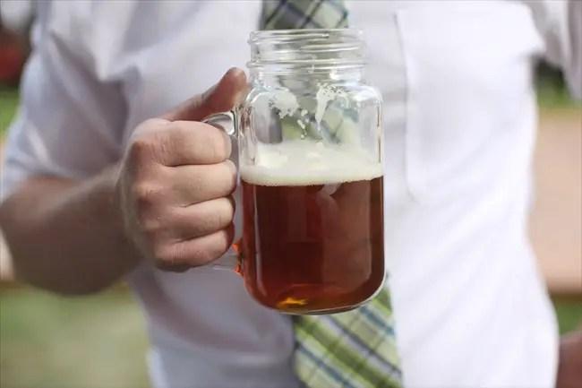 Mason Jar Beer Mug held by guest at wedding reception