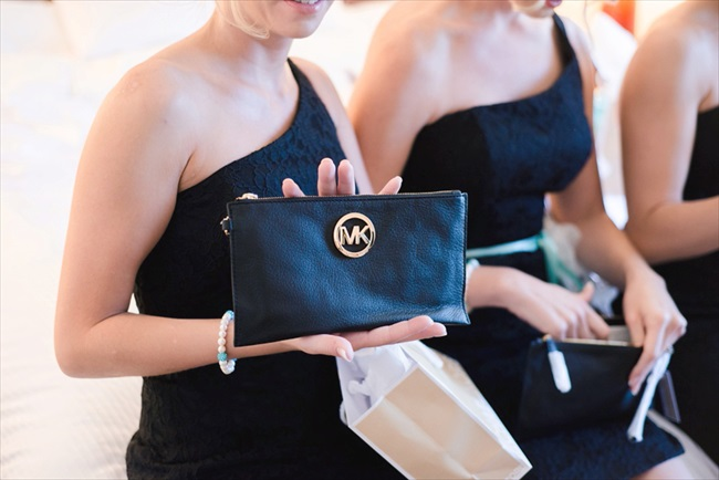 the bridesmaids received customized clutch purses in black.  their bridesmaid dresses were black with a one shoulder style neckline