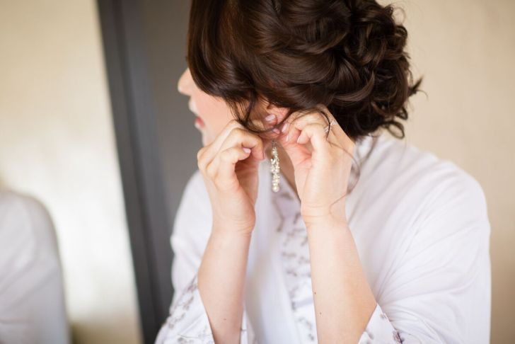Winery Styled Wedding Shoot - The Bride in Robe Putting on Earrings