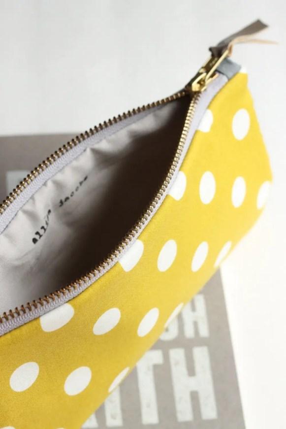 allisa jacobs yellow polka dot zipper clutch