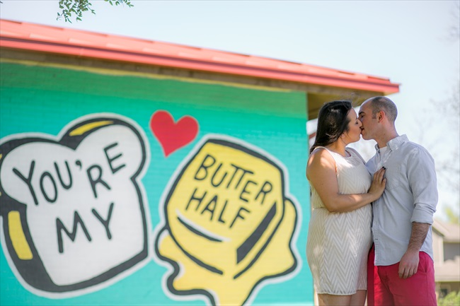 couple kisses by graffiti saying
