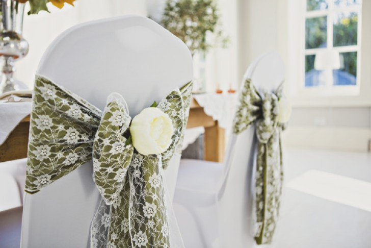 lace bows with flowers on the backs of chairs