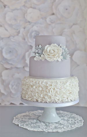 grey wedding cake three tiers with flowers made of icing covering the entire bottom layer