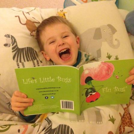 child in bed laughing reading flu bug
