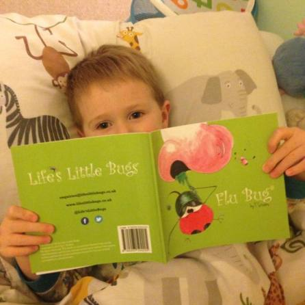 child in bed reading flu bug