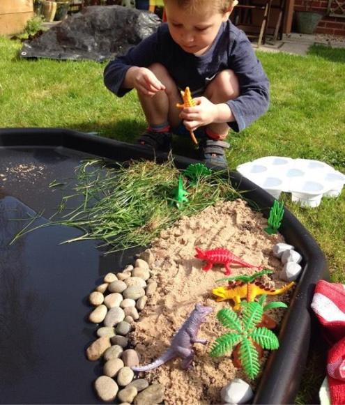 child playing with dinosaurs on a tuff tray