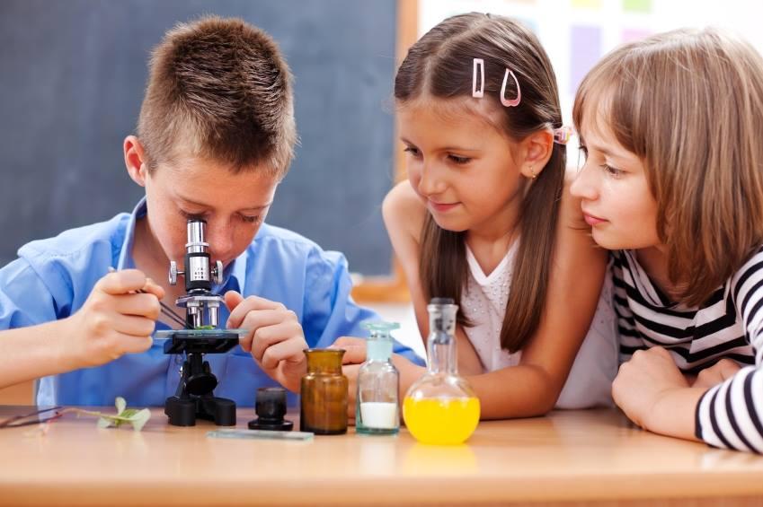 3 children around a microscope