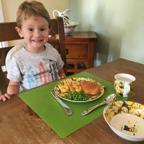 Jake smiling with his new dinner set and dinner