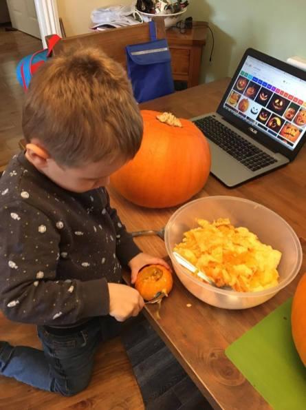 Jake carving his small pumpkin