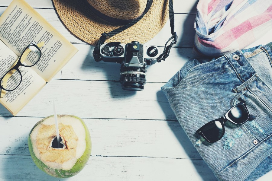 flat lay of camera, jeans, sunglasses, scarf, summer hat and book