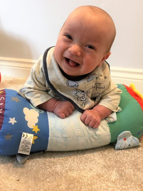 smiling baby doing tummy time