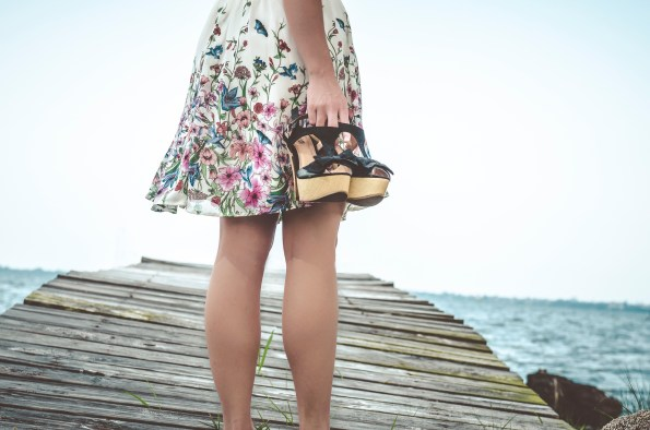 girl in skirt holding sandals