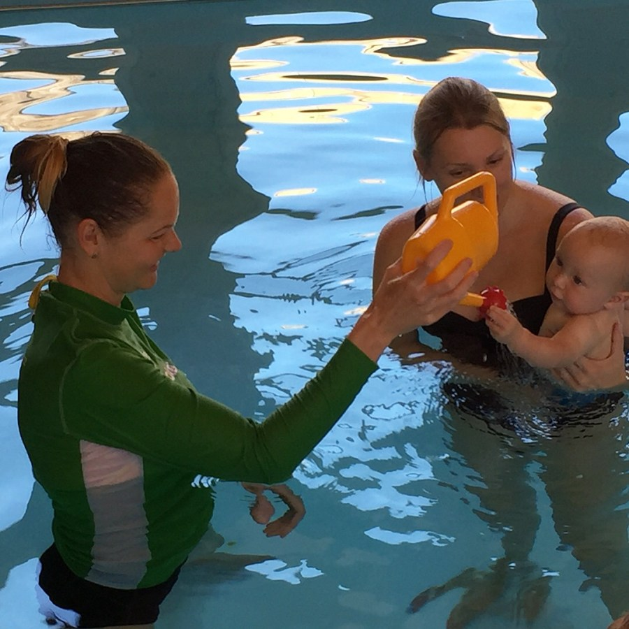 swimming teacher holding a toy watering can to a Mum and baby