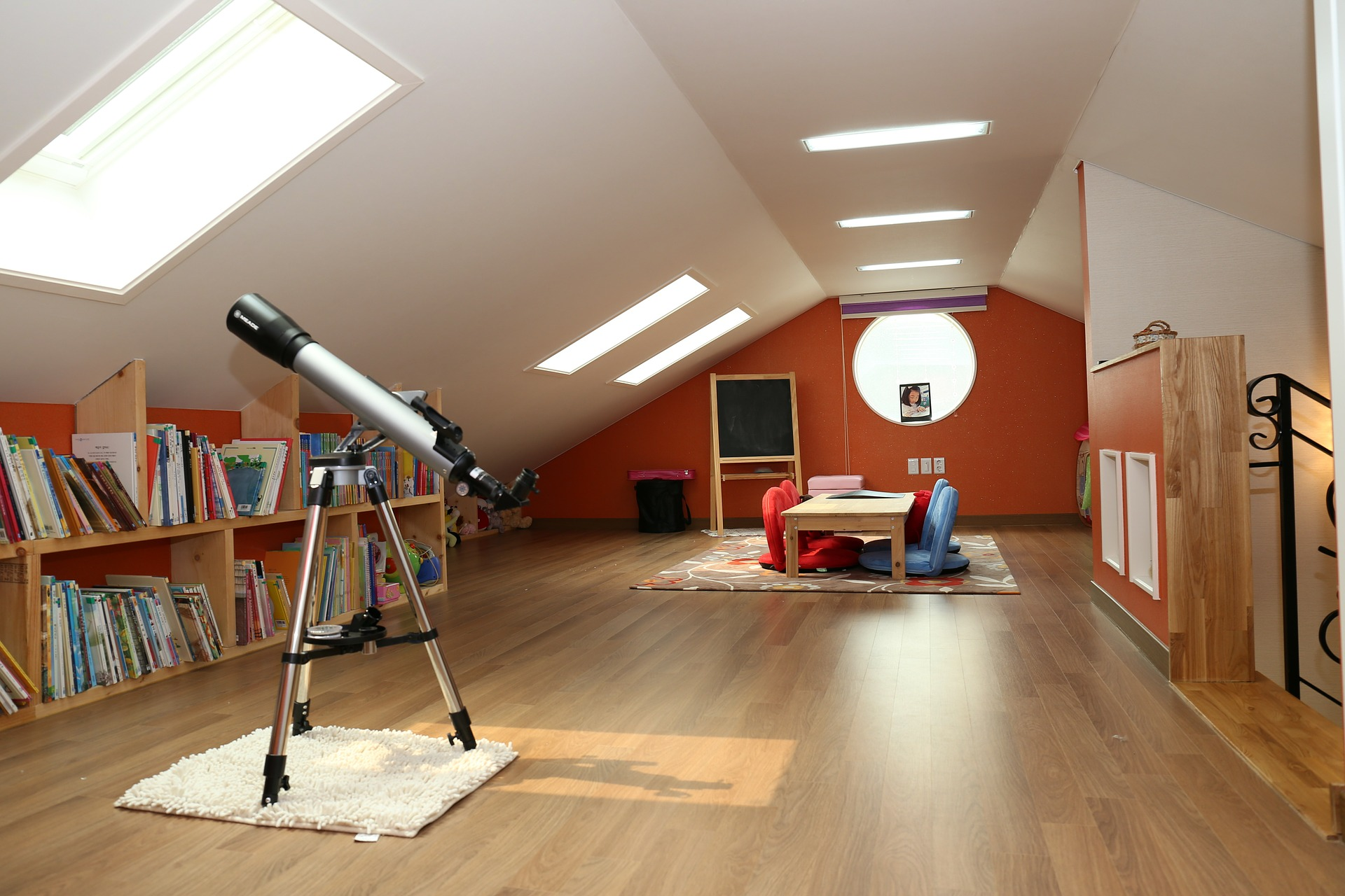 loft conversion room with books, open space and telescope