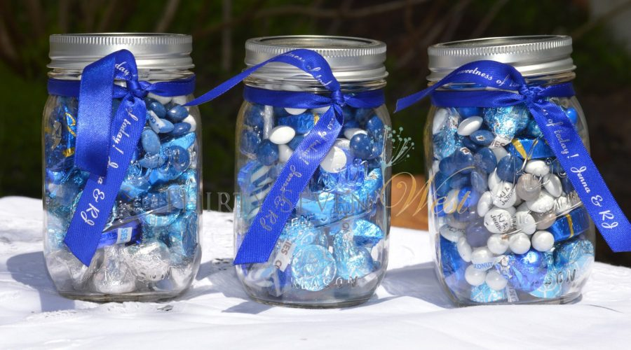 glass jars full of sweets and blue ribbons wrapped around