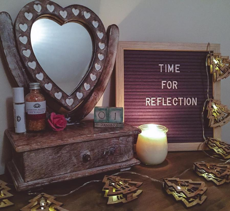 a dressing table with a heart shaped mirror and a peg board with the words time for reflection written on it. There is a lit candle and xmas tree lights draped across the surface